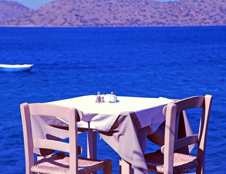 traditional greek outdoor restaurant with Mediterranean sea view(Crete, Greece). Toned image photo