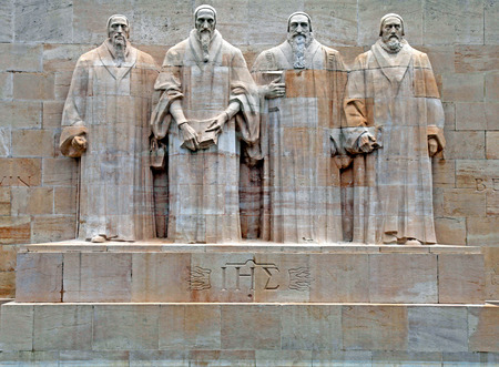 Reformation wall in Parc Des Bastions, Geneva, Switzerland. Sculptures of the four great figures of the geneva protestant movement : Guillaume Farel (1489 - 1565), Jean Calvin (1509-1564), Theodore de Beze (1513-1605) and John Knox (1513-1572) , Geneva, S Editorial