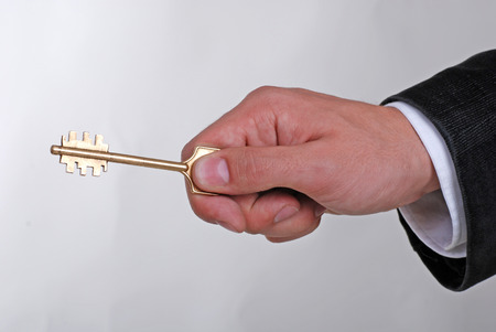 Businessman with a golden key in his hand on grey background photo