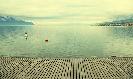 Empty gray wooden pier on Lake Geneva, Montreux, Switzerland. Toned image photo