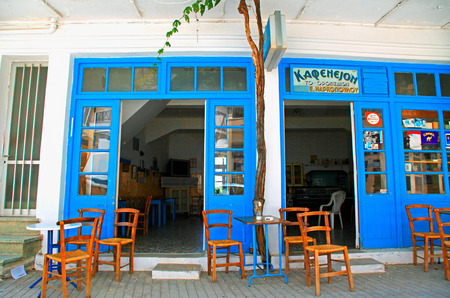 CRETE, GREECE - JULY 17, 2012: Traditional old Greek cafe tavern with blue doors and chairs on sidewalk,Crete, Greece.
