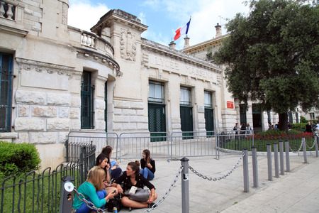 academie: NICE, FRANCE - MAY 14,2013: Young girl students sitting before Lycee Massena, Nice, Provence-Alpes-Cote dAzur, France. Editorial