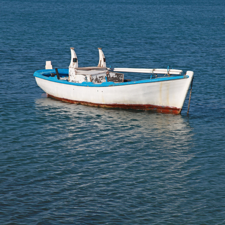 Blue and white old wood boat at a Mediterranean sea(Greece) Square image photo