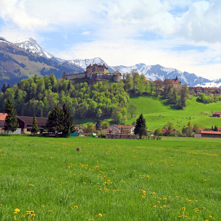 summer beauty: Beautiful landscape with Gruyere Castle, fields and Alps Mountains in the background, Switzerland Editorial
