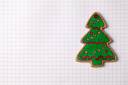squared: Handmade painting wood christmas tree decoration on white squared paper background with copy space