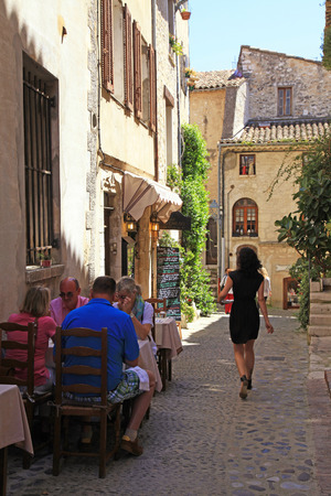 SAINT-PAUL-DE-VENCE, FRANCE - MAY 12, 2013: People at outdoor cafe on beautiful narrow street in Saint Paul de Vence, one of the oldest towns of the Provence, France, famous town of painters and galleries.