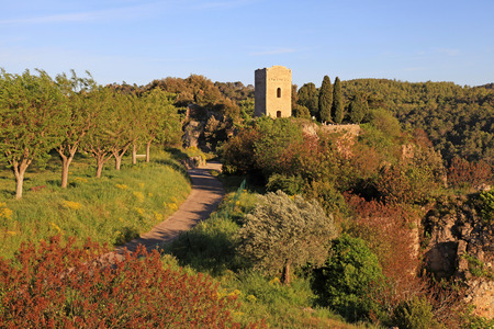 View on medieval tower in village with rural landscape, Provence, France. Sunrise light photo