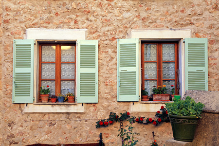 Two french rustic windows with old green shutters and flower pots in stone rural house, Provence, France. photo