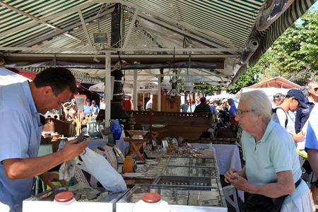 collectibles: NICE, FRANCE - MAY 13,2013: People shopping at the famous of antique market  Cours Saleya every Monday, French Riviera, Nice, France. Huge variety of collectibles is on offer: silver, crystal,ceramics, paintings,etc