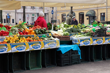 checking ingredients: LJUBLJANA, SLOVENIA - FEBRUARY 10, 2015:  People sells fruit and vegetables at local farmer market in center of Ljubljana, Slovenia. Editorial