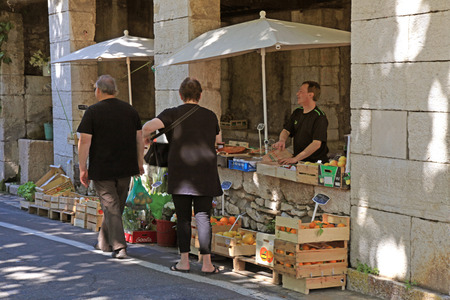 checking ingredients: SAINT-PAUL-DE-VENCE, FRANCE - MAY 12, 2013: People buy fruit and vegetables at local farmer market in Saint Paul de Vence, Provence, France.