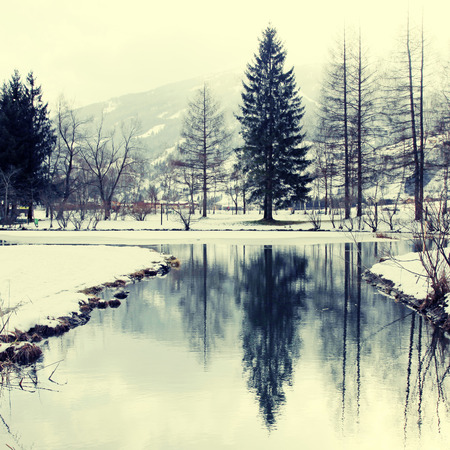 Winter landscape with trees and pond reflection in Alps mountains, Austria. Square toned image, instagram effect photo