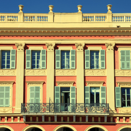 cote d'azur: Beautiful ornate red building facade with traditional shutter windows in the city of Nice,Cote dAzur,  France. Square toned image Editorial