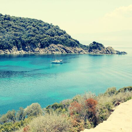 beach scene: Mediterranean landscape with beautiful turquoise bay, Ammouliani island, Halkidiki. Square toned image.