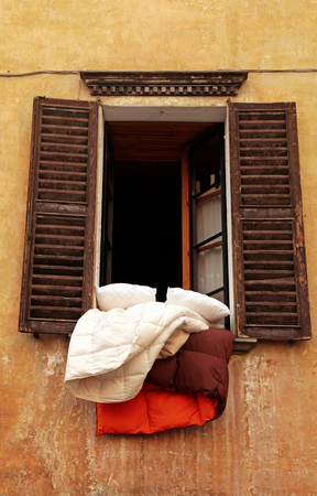 bedclothes: Open old window with wood shutters, grungy wall and bedclothes in small town, Italy
