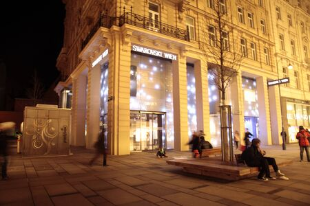 swarovski: VIENNA, AUSTRIA - FEBRUARY 3, 2015:  View of main shopping street Graben at night with tourists and Swarovski shop in Vienna, Austria. Motion blur