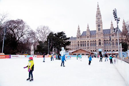 establishes: VIENNA, AUSTRIA - FEBRUARY 4, 2015: Ice skating people at the Wiener Eistraum (ice rink). The town government establishes every winter an ice rink in front of the Viennese city hall, Vienna, Austria