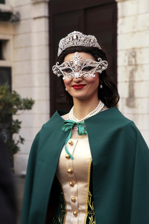 venecian: VENICE, ITALY - FEBRUARY 8, 2015: Beautiful unidentified masked woman in costume on San Marco Square during the Carnival in Venice, Italy.