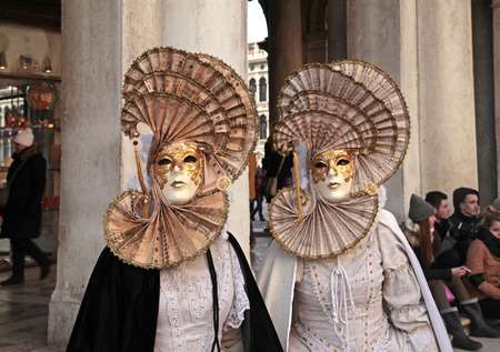 VENICE, ITALY - FEBRUARY 7, 2015: Two unidentified masked persons in costume on San Marco Square during the Carnival in Venice, Italy. Editorial