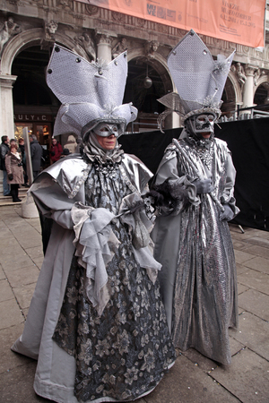 venecian: VENICE, ITALY - FEBRUARY 8, 2015: Two unidentified masked persons in costume on San Marco Square during the Carnival in Venice, Italy. Editorial
