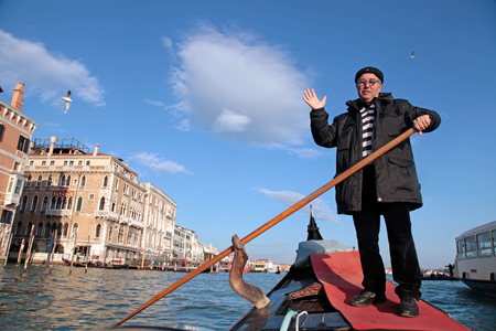 gondolier: VENICE, ITALY - FEBRUARY 7, 2015: Smiling gondolier in his gondola on the Grand Canal, Venice, Italy Editorial