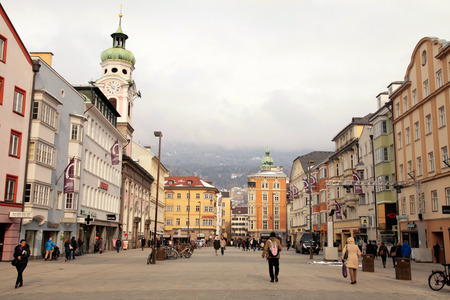 INNSBRUCK, AUSTRIA - FEBRUARY 5, 2015: People visit the Old Town with the Stadtturm (City Tower) and other famous historical houses in Innsbruck, Austria.