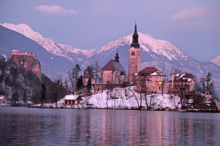 Winter landscape of Bled Lake and island church, Slovenia. Sunset light