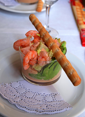 breadstick: shrimp cocktail in pink sauce with salad and breadstick. selective focus