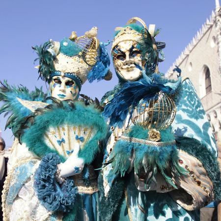 mascara de carnaval: VENECIA, Italia - FEBRERO 8, 2015: Dos personas no identificadas enmascarados magnífico traje de la turquesa en la Plaza de San Marcos durante el Carnaval de Venecia, Italia. imagen cuadrada Editorial