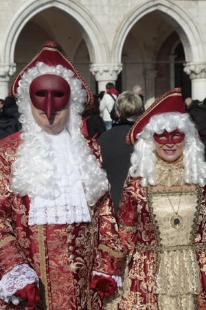 mascara de carnaval: VENECIA, Italia - 08 de febrero 2015: Dos personas no identificadas enmascarados en magnífico traje rojo y oro en la Plaza de San Marcos durante el Carnaval de Venecia, Italia.