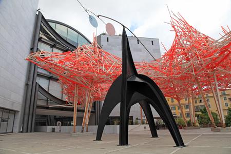 """arte moderno: NIZA, FRANCIA - 14 de mayo 2013: la instalación de madera y el arte de metal llamado """"Hommage à Alexander Calder 'y la fachada del Museo de Arte Moderno y Contemporáneo (MAMAC), importante referente cultural y turístico en Niza, Francia."""