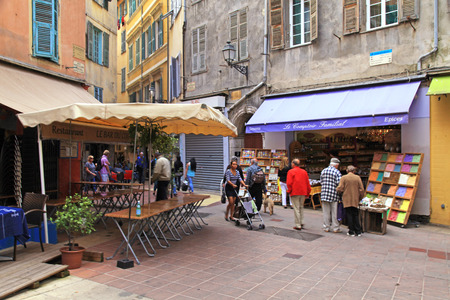 nice day: NICE, FRANCE - MAY 14, 2013: Tourists and local people walking on the charming vintage streets of Old town in Nice, France. Selective focus