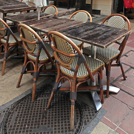 cote d'azur: french outdoor cafe with wood tables and wicker chairs,Nice, Cote dAzur, France. Square image