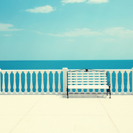 Summer view with classic white balustrade, bench and empty terrace overlooking the sea (Italy). Square toned image, photo