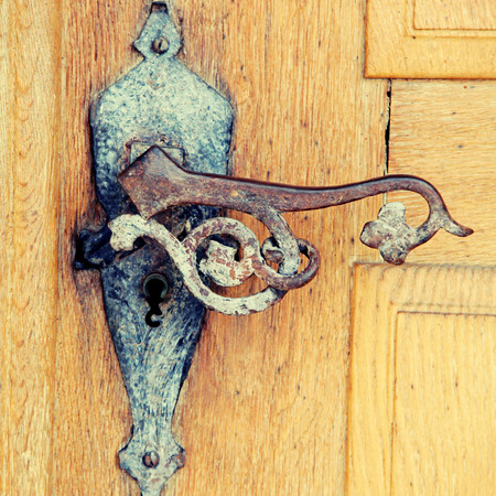 Old rusty iron handle in medieval door, square toned image,  selective focus photo