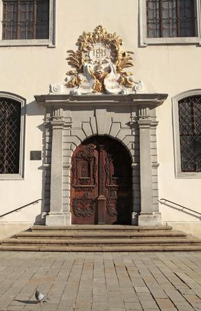 sacerdote: La Iglesia de los Jesuitas (Santo iglesia del salvador) de entrada con puerta de madera decorado en el casco antiguo de Bratislava, Eslovaquia Foto de archivo