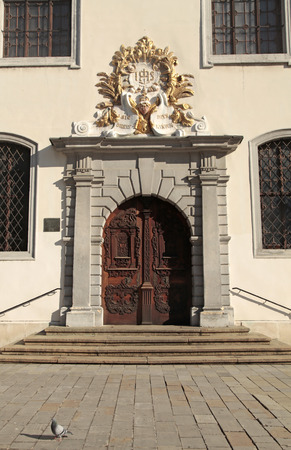 priest: The Jesuit Church (Holy Saviour Church) entrance with decorated wood door in the Old Town of Bratislava, Slovakia