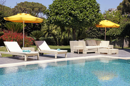 庭園のスイミング プールの近くの屋外用家具ホワイトが美しい夏のリゾート地でリラックスします。 写真素材