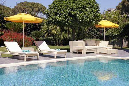 Muebles de exterior blanco en el jardín cerca de la piscina para relajarse en hermoso lugar de veraneo Foto de archivo - 41949163