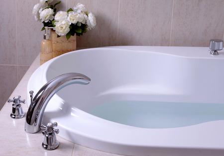 detail of bathroom, white bath tub with faucet and beige mozaic tiles, selective focus Foto de archivo