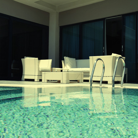 beautiful swimming pool with white outdoor furniture on modern luxury resort square toned image