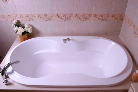 en suite: white bath tub with faucet and beige tiles in bathroom