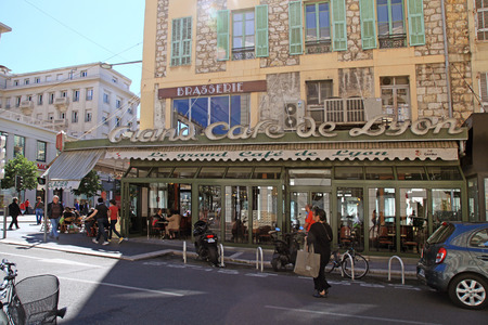 french cafe: NICE, FRANCE - MAY 13, 2013: Outdoor french cafe in old building on the main city street - Jean Medecin Avenue in Nice,France. Sunlight Editorial