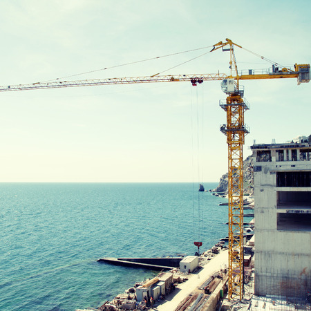 onsite: Tall yellow crane on construction of the new expensive apartment building on the sea coast(Crimea,Ukraine). Square toned image, instagram effect
