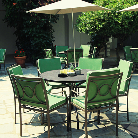 tree detail: Iron tables and chairs with parasol in beautiful mediterranean patio cafe. square toned image,  effect