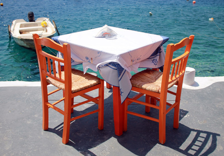 santorini island: greek tavern with orange wooden chairs by the sea coast, Greece, Santorini island in Cyclades
