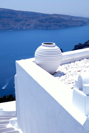 greek pot: Bianco tradizionale pentola greca su terrazza bianca con vista sul Mar Egeo in background, Oia, isola di Santorini, Cicladi, Grecia Archivio Fotografico