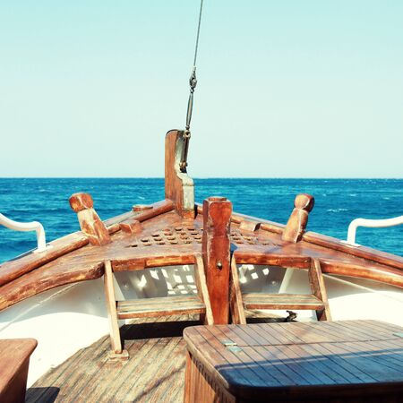 ship bow: The bow of old wood ship in blue waters of Mediterranean sea, square toned image