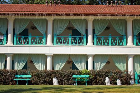 scenary: facade of summer resort villa with balconies in scenary garden Stock Photo