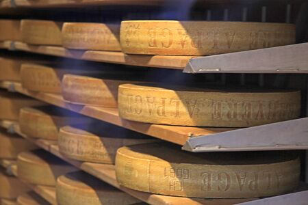 matures: GRUYERES, SWITZERLAND - MAY 8, 2013: Famous Swiss cheese matures at the shelfs of cheese dairy in Gruyeres, Switzerland. Selective focus